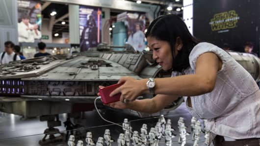 A visitor takes a selfie with a model of the Millennium Falcon from the Star Wars movies at the 17th Ani-Com and Games exhibition in Hong Kong on July 24, 2015.